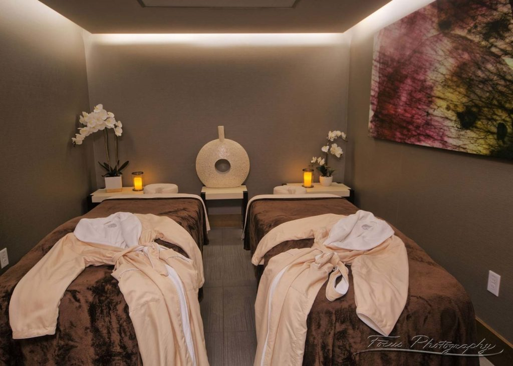 two massage beds covered with soft linens and spa robes in candle lit room