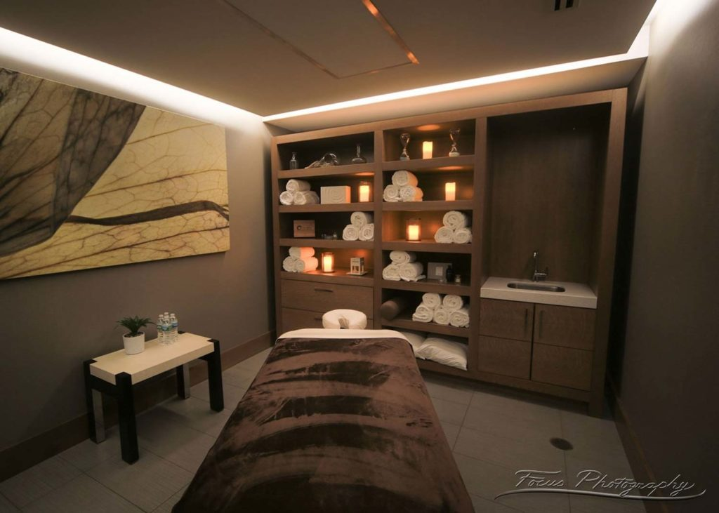 one massage beds covered with soft linens and spa robes in candle lit room