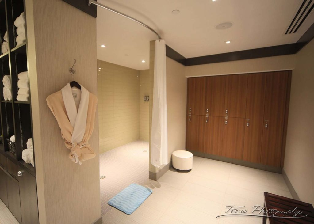 luxury spa room locker room with fresh towels, bath robes, lockers and large shower