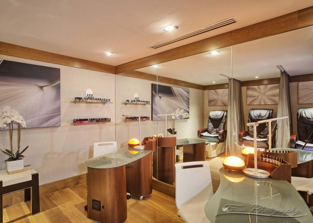 inside artne spa's nail salon room with client tables and shelves of nail polish colors